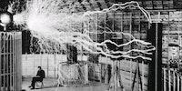 Nikola Tesla sitting in his laboratory with his Magnifying Transmitter