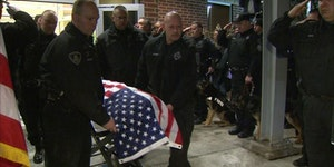 Slain K-9 officer being led out of veterinary hospital in coffin. His name was Rocco.