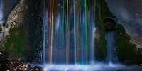 Long exposure shot of glow sticks dropped into a waterfall.