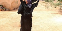 Removing a niqab after her city is freed from Isis control