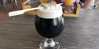 A s'mores porter with a burnt marshmallow stuck in it.