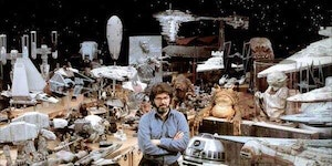 George Lucas surrounded by Star Wars props, 1977