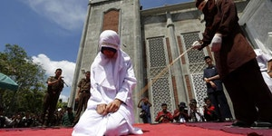 An Indonesian girl being publicly whipped for violating Shari'a law.
