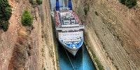 A cruise ship is guided through the Corinth Canal, Greece.