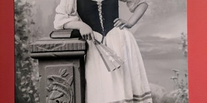 A very bored looking Andy Samberg hanging out as a woman in the 1800's.